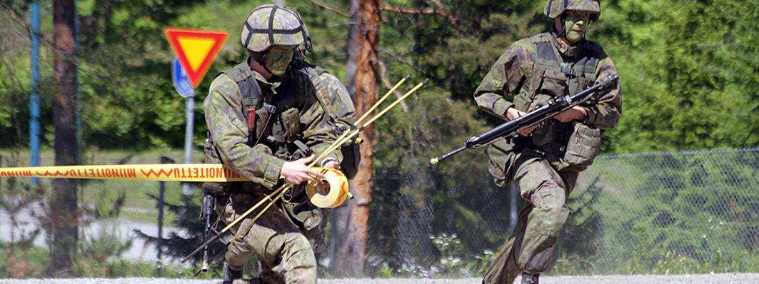 Kaksi sotilasta juoksee vasemmalta oikealle.
