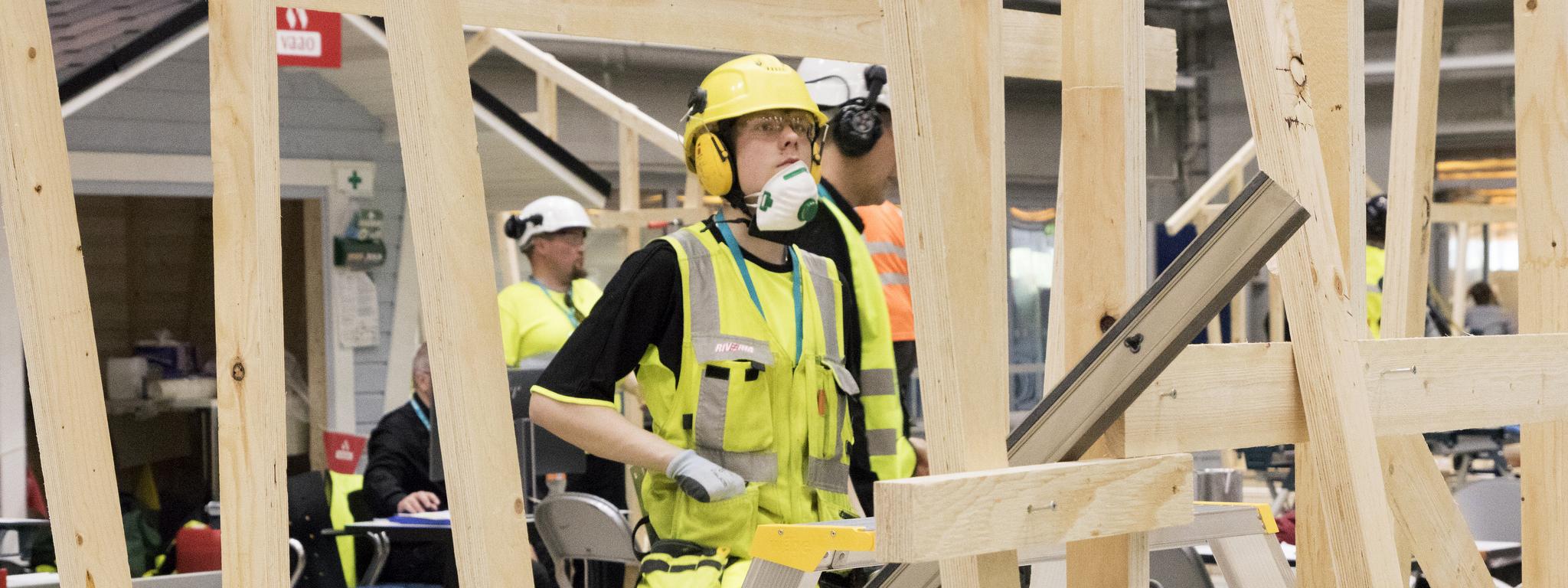 Nuori mies katselee hökkeliä, jota on rakentamassa.