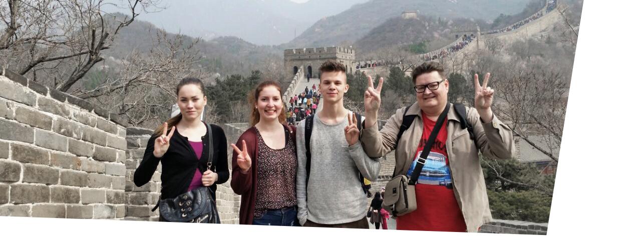 Ihmisiä Kiinan muurilla näyttämässä rauhanmerkkiä.