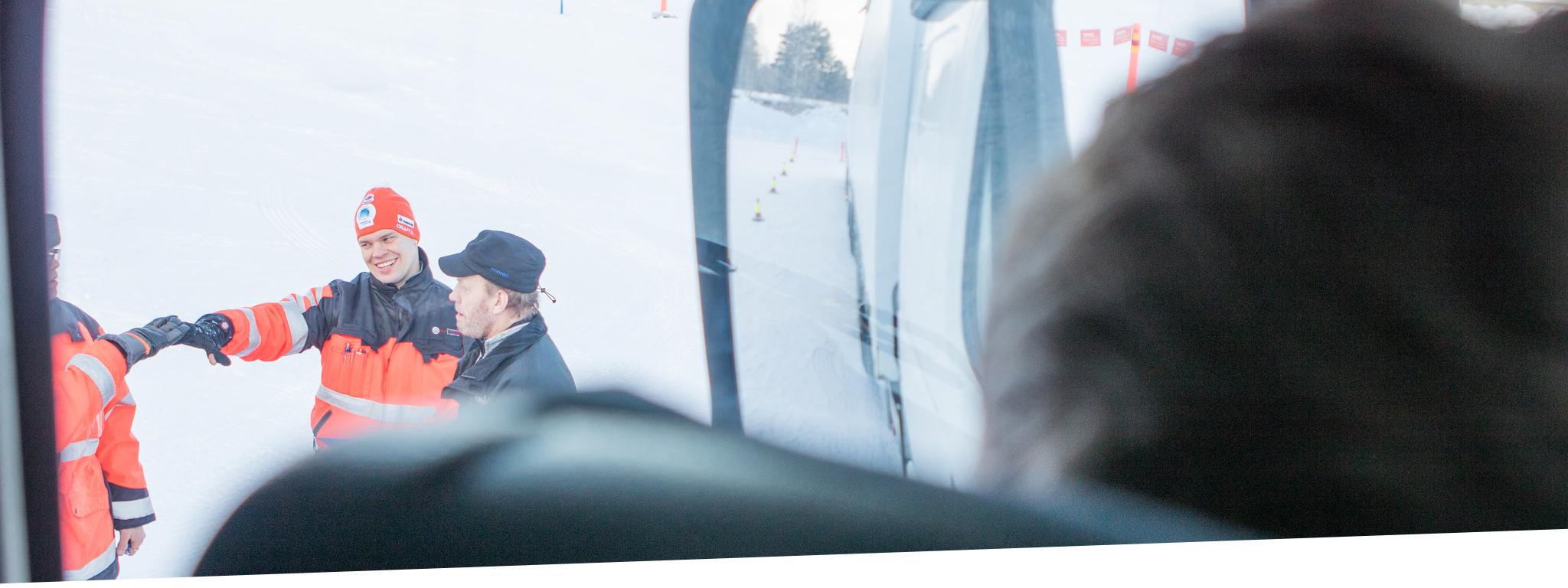 Kuva on otettu rekan sisällä. Ulkona miehet iskevät kädet yhteen hymyillen. Talvikuva.