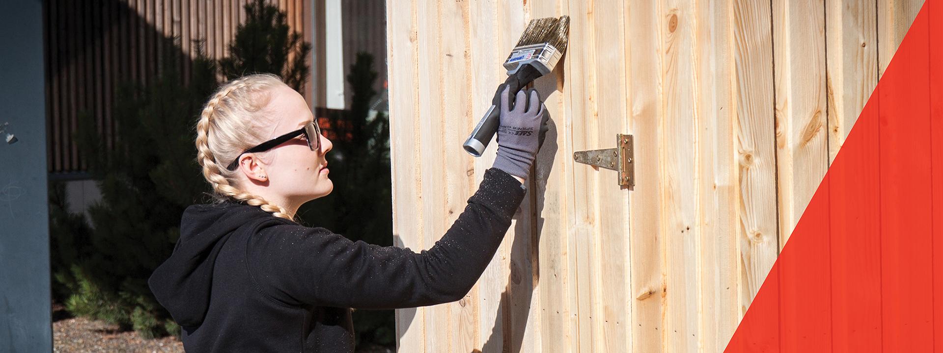 Tyttö maalaa siveltimellä puuseinää