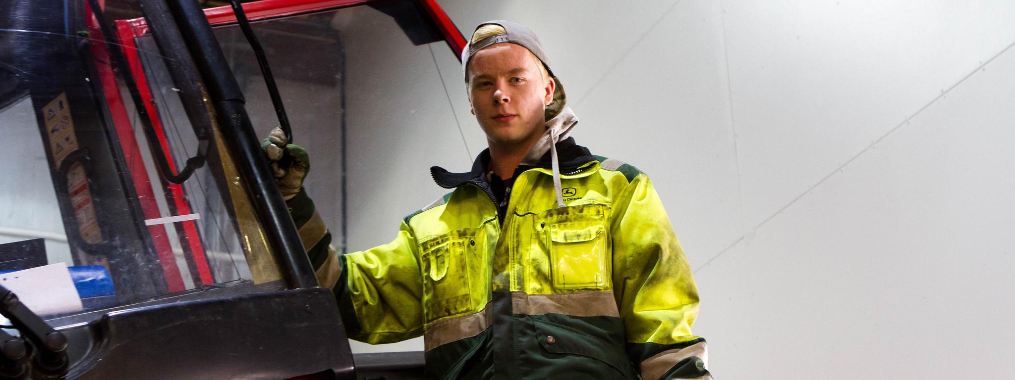 Nuorimies metsäkoneen vierellä likaisissa vaatteissa joissa on John Deeren logo.