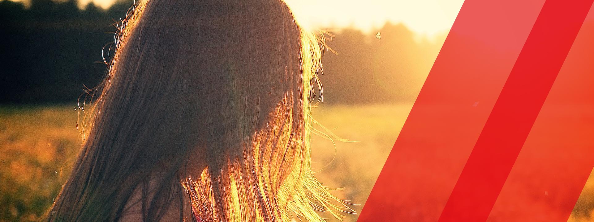 nainen kesäisellä pellolla, aurinko paistaa oikealta.