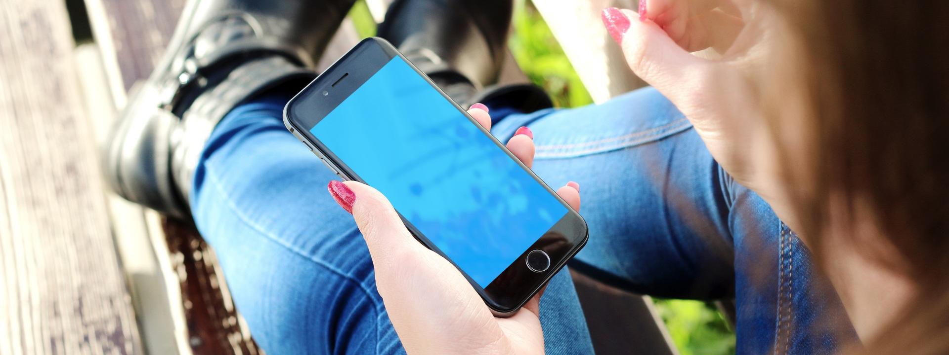 Naisella on älypuhelin kädessään.