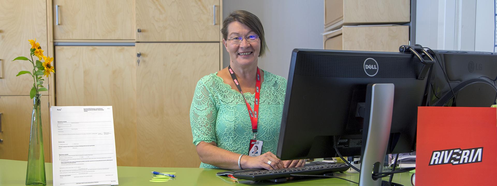 Nainen hymyilee pöydän takanava, opintotoimisto Riveria