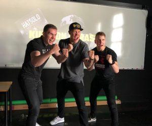 Kolme miestä nyrkit pystyssä. Ovat innoissaan.