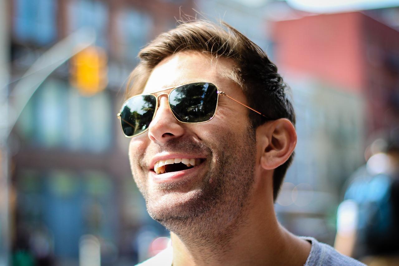 Mies nauraa aurinkolasit päässään.