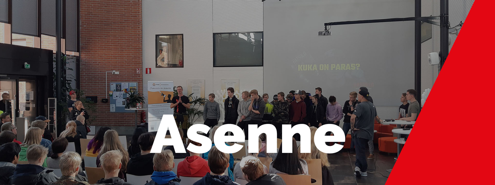 Kuva opiskelijaryhmästä ja opettajasta. Taustalla taululla lukee KUKA ON PARAS? kuvassa lukee isolla ASENNE.