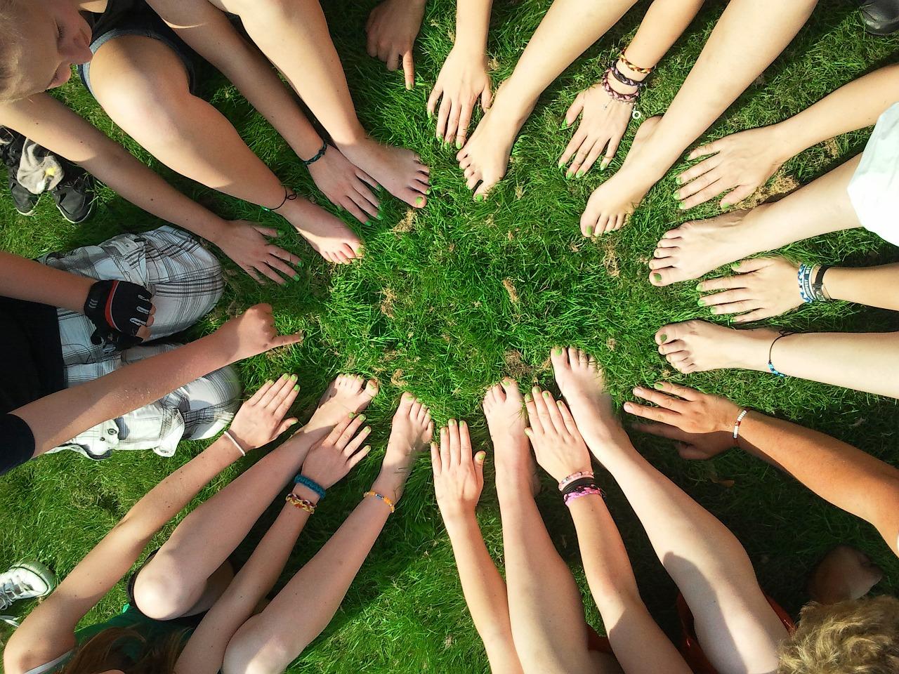 Käsiä ringissä vihreällä nurmella.